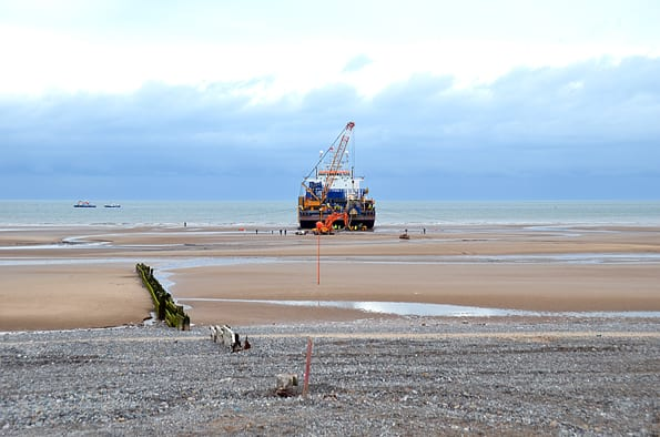 Cable barge lined up with buoys on beach